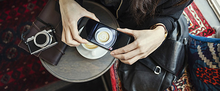 Woman photographing coffee.