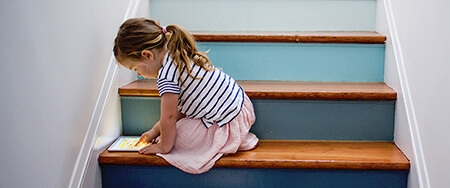 Girl tablet on staircase.