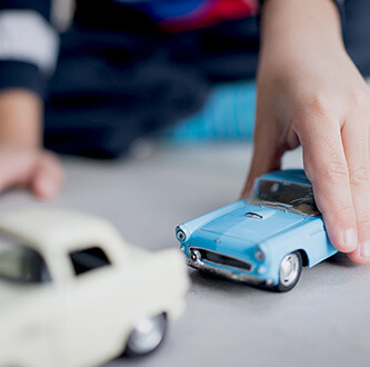 Boy playing with cars.